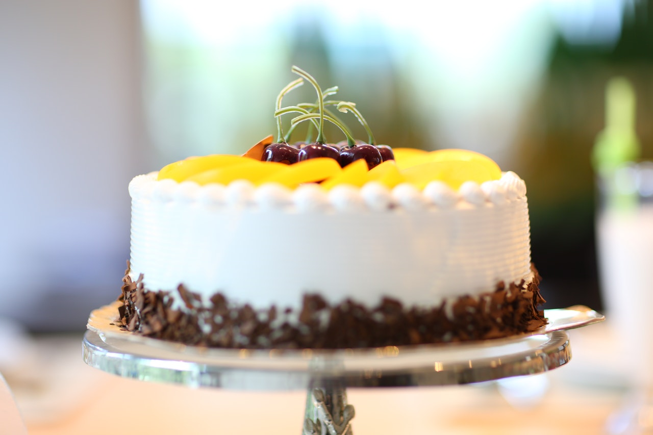 White round cake topped with yellow sliced fruit