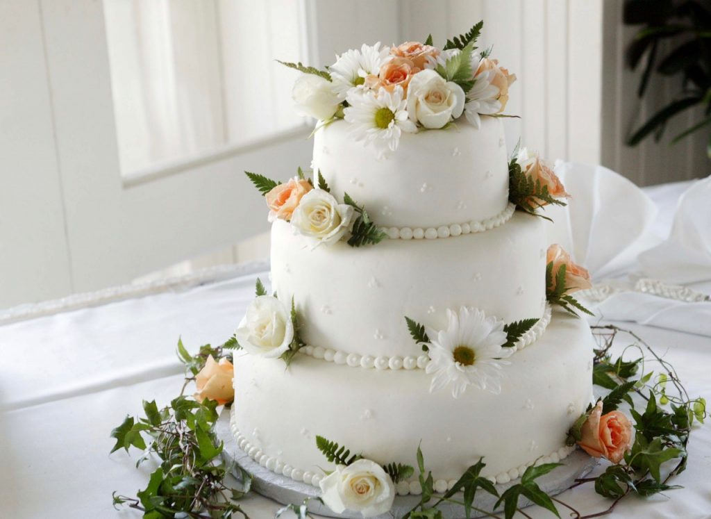 White wedding cake with flower decorations