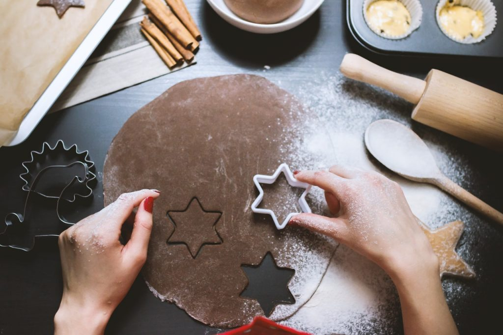 A woman cutting out a star on a dough