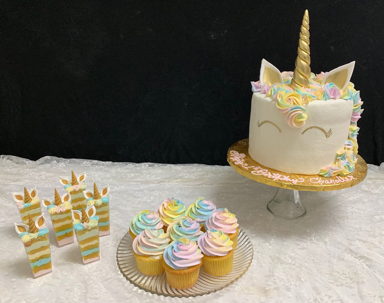 Unicorn-inspired cake, cupcakes and sliced cake on top of a white table linen