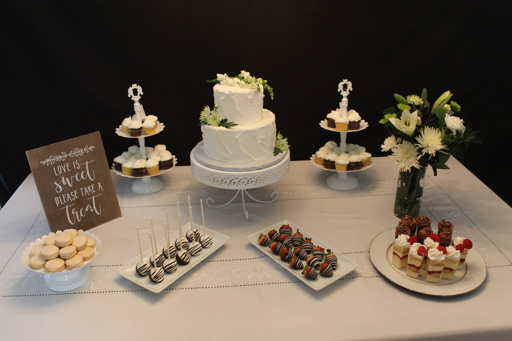 Table full of desserts and a white wedding cake