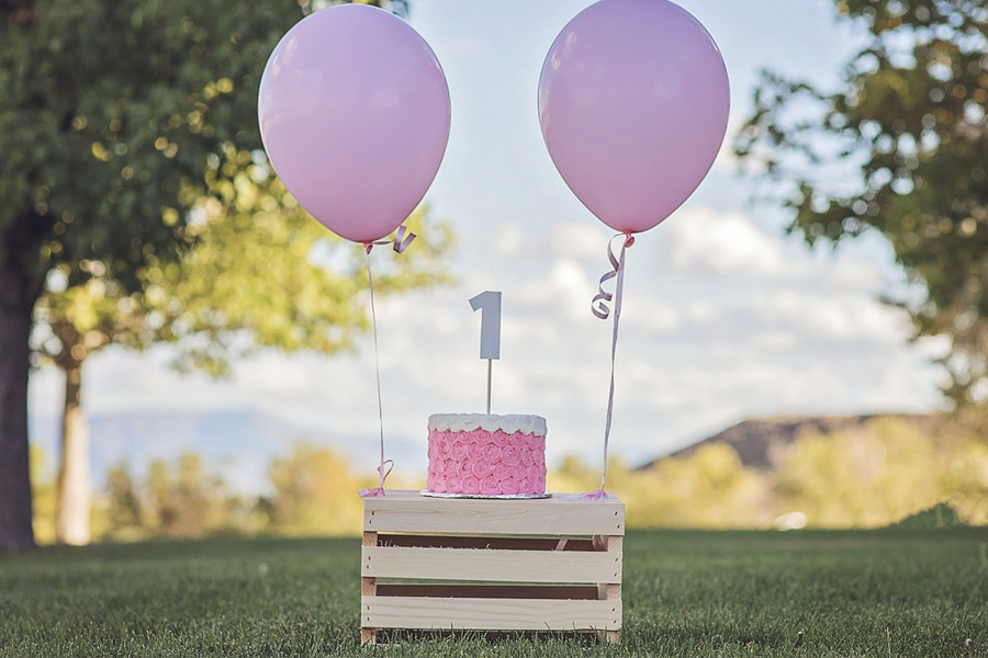 pink sweets on top of a table with two balloons