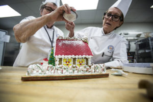 Two chefs decorating a cake
