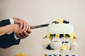 bride and groom cutting the perfect brides cake like this one with cupcakes and a solid top cake decorated with floral accents