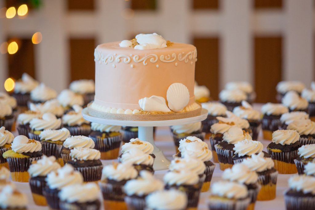 A pale pink wedding cake on a pedastool surrounded by cupcakes.