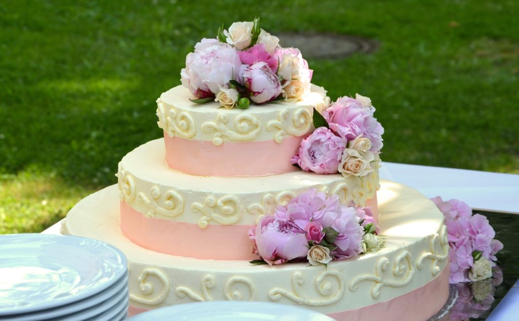 A pink and white wedding cake on a table outside.